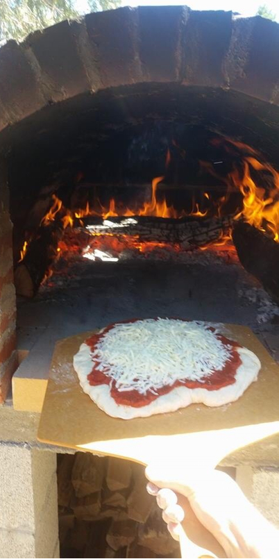 Cooking pizza in stone oven.